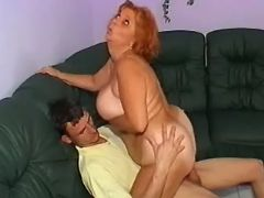 Redhead granny sucks cute guy and rides him cock
