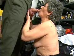 Lewd grandma greedily sucking fat cock in workshop
